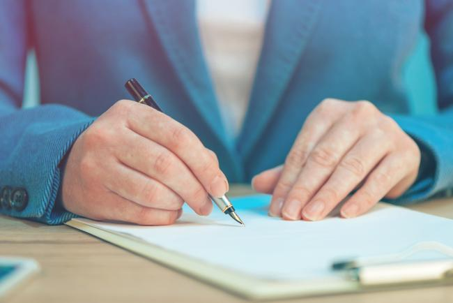 18184255-close-up-of-female-hands-writing-signature-on-business-agreement.jpg