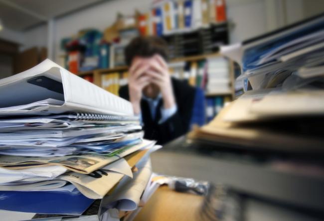 18286996-frustrated-man-sitting-desperate-over-paper-work-at-desk_0.jpg