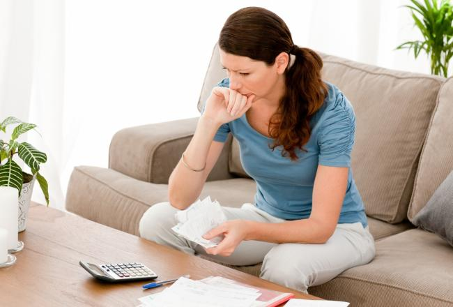 3657037-stressed-woman-calculating-her-bills-sitting-on-the-sofa.jpg