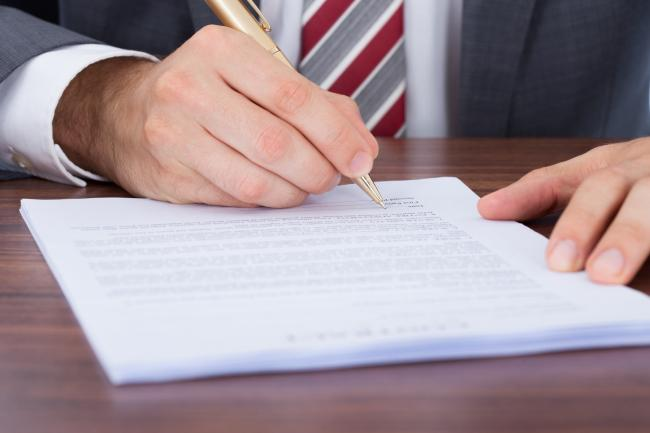 9801631-businessman-signing-document-at-desk.jpg