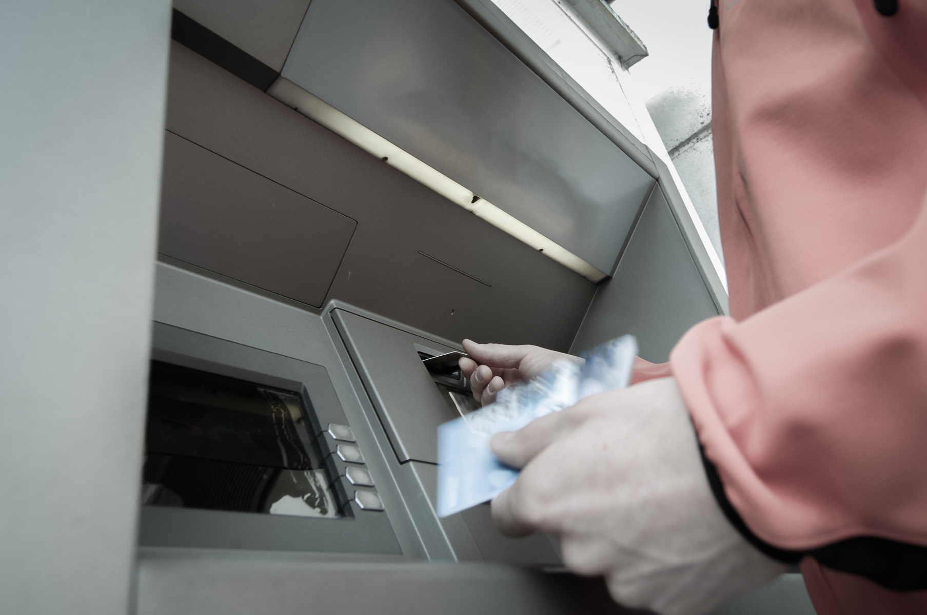 16308103-man-at-atm-machine-with-stash-of-credit-and-debit-cards.jpg