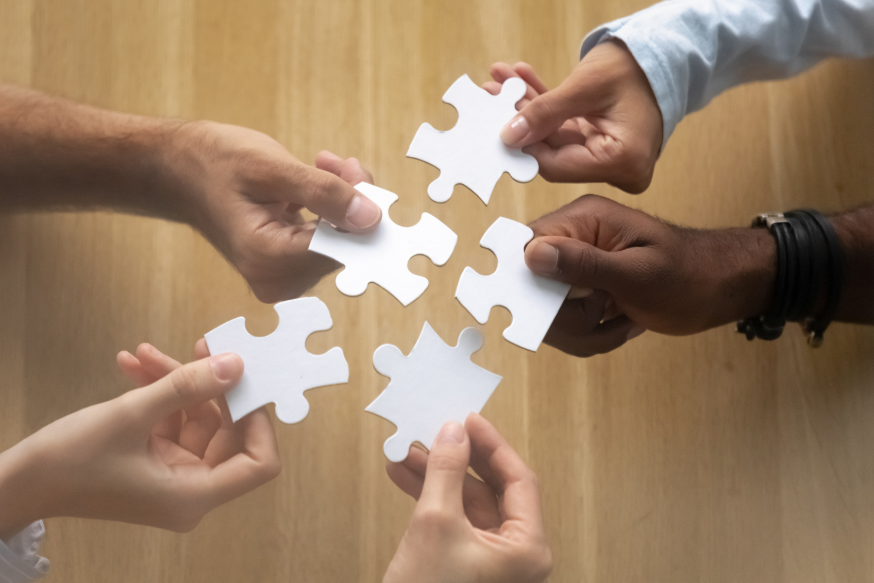 36223097-hands-of-diverse-team-members-assembling-jigsaw-puzzle.jpg