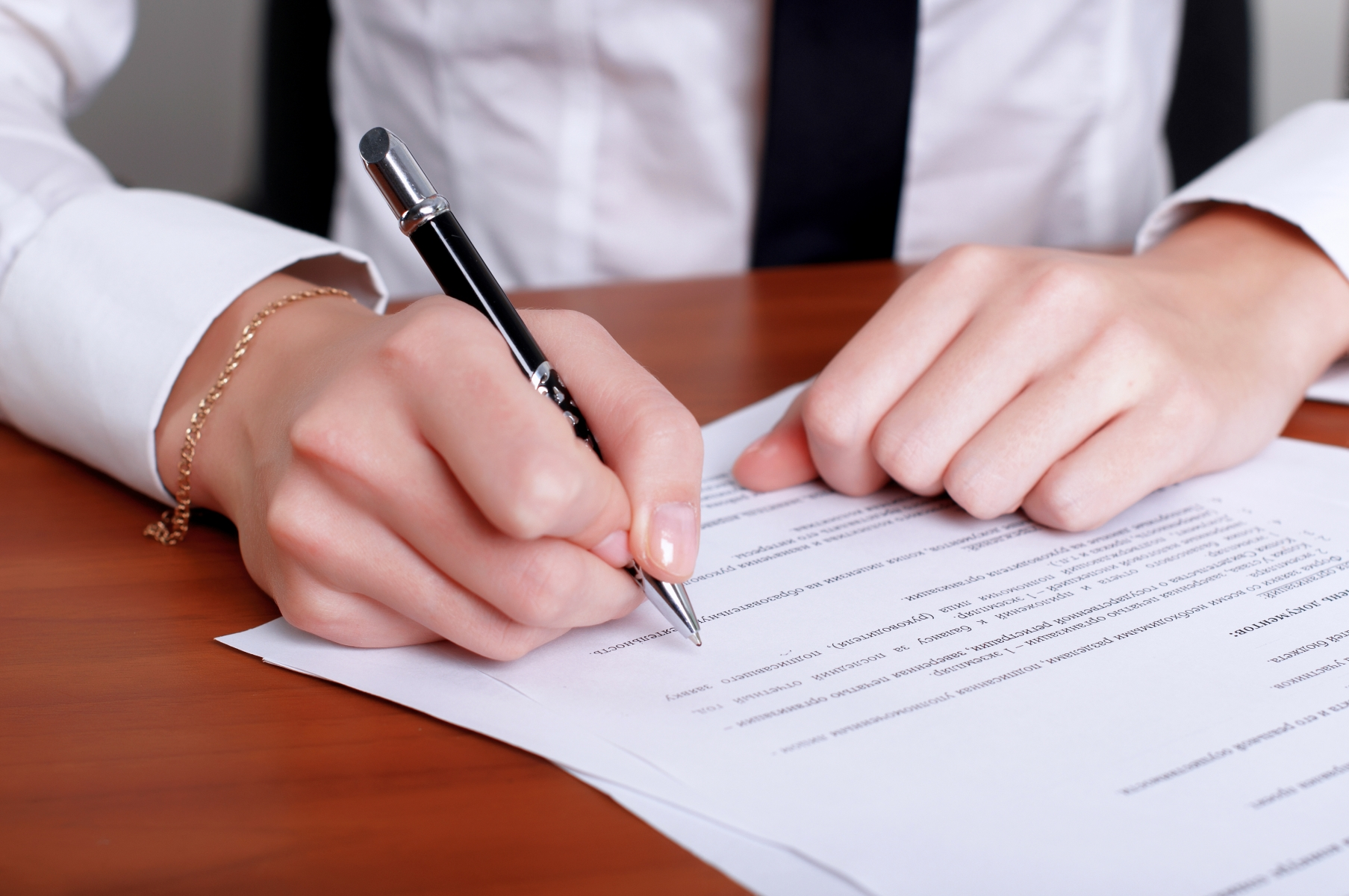 1047509-person-s-hand-signing-document.jpg