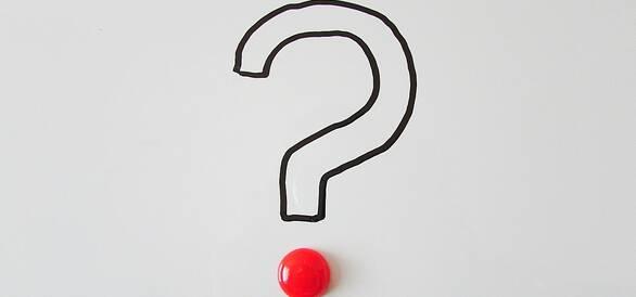 Foto på ett ritat frågetecken med en röd plupp