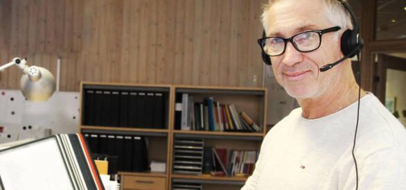 Man med headset vid skrivbord