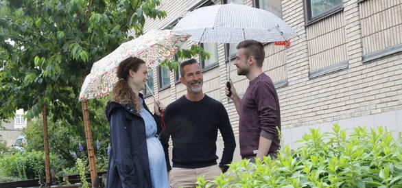 tre personer med paraplyer