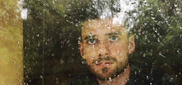 Ung kille tittar ut genom ett fönster.