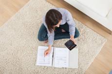 9803426-woman-calculating-home-finances-on-rug.jpg