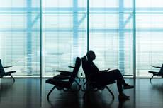 12275760-woman-in-transit-waiting-on-airport-gate.jpg