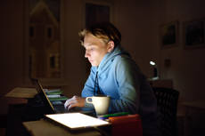 42798518-concentrated-young-man-working-night-at-home-office-with.jpg